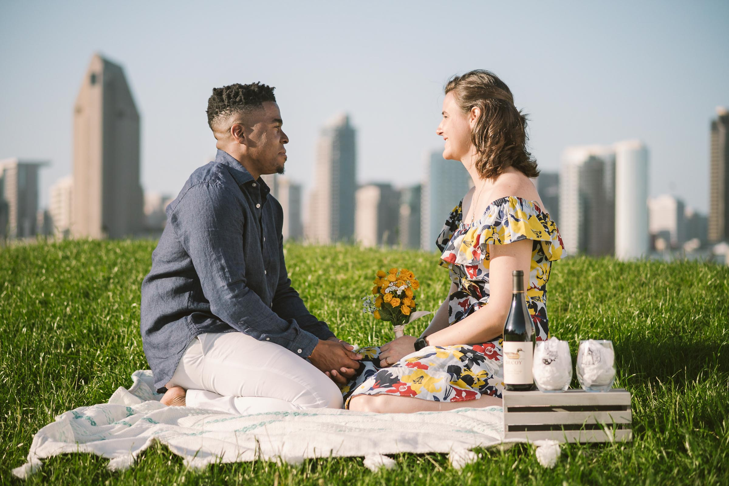 engagement session coronado island picnic san diego skyline california props yellow flowers grass wine glasses