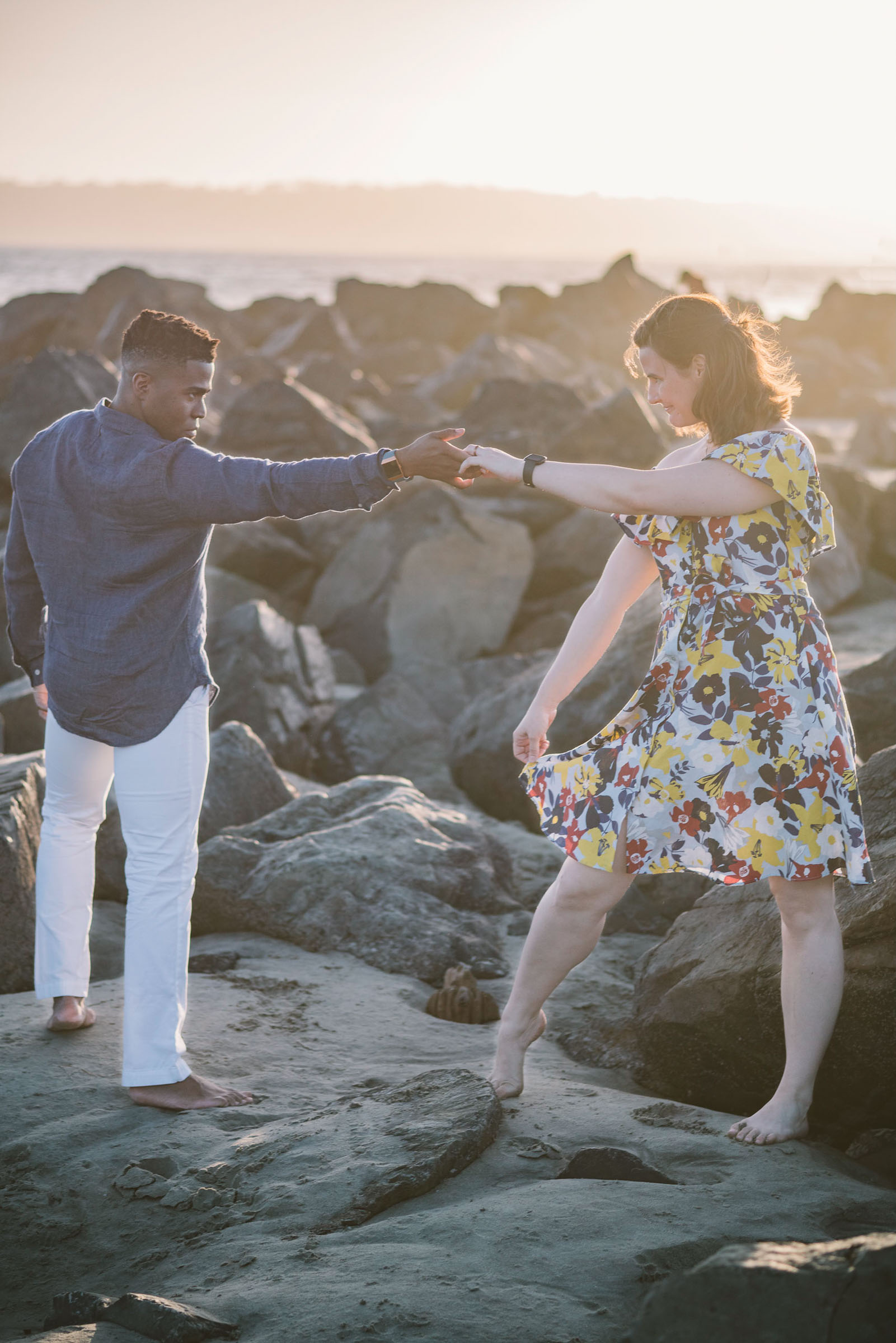 engagement session coronado island sunset san diego california white girl yellow blue red dress african american interracial couple rocks dancing