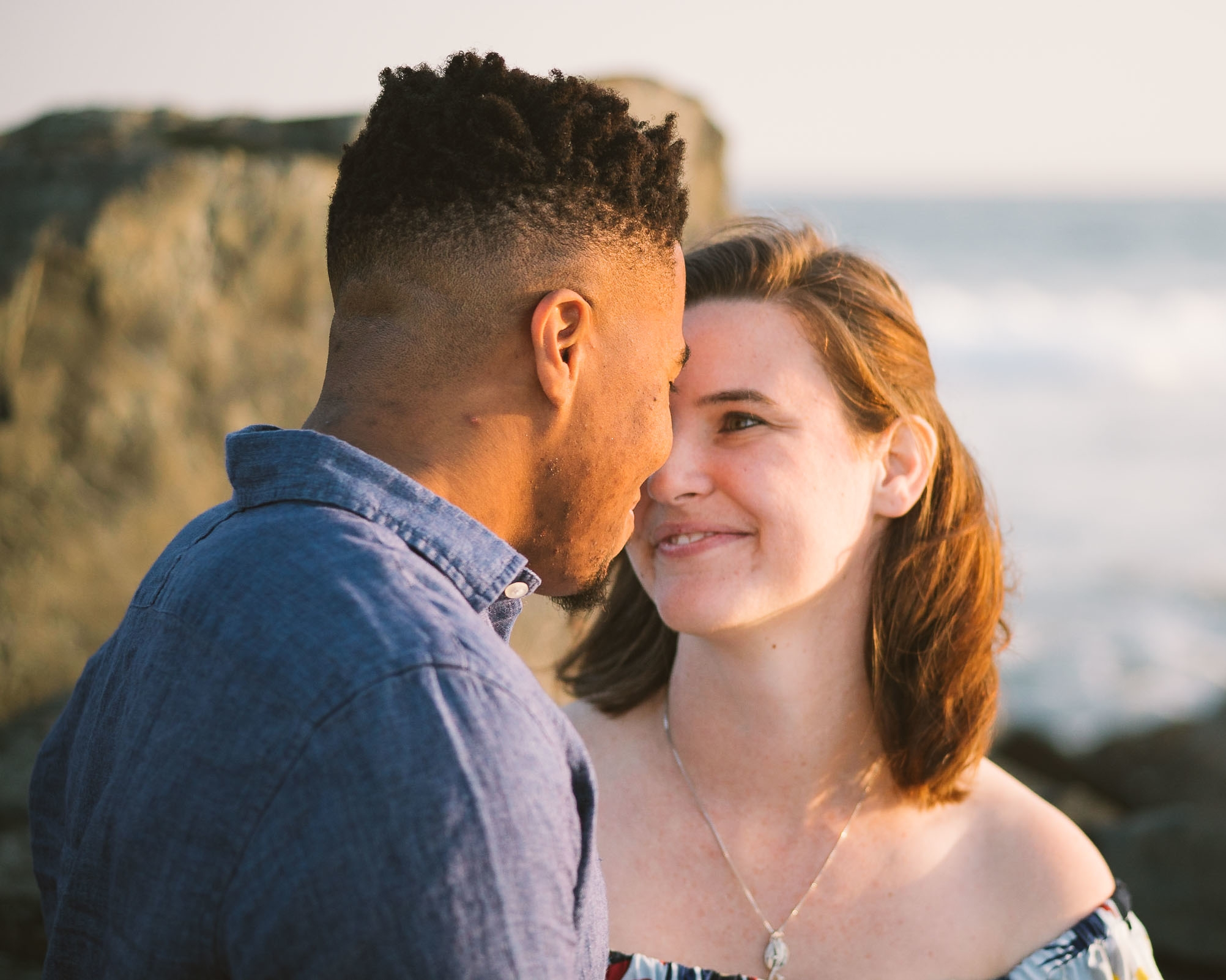 engagement session coronado island sunset san diego california white girl yellow blue red dress african american interracial couple rocks head boop