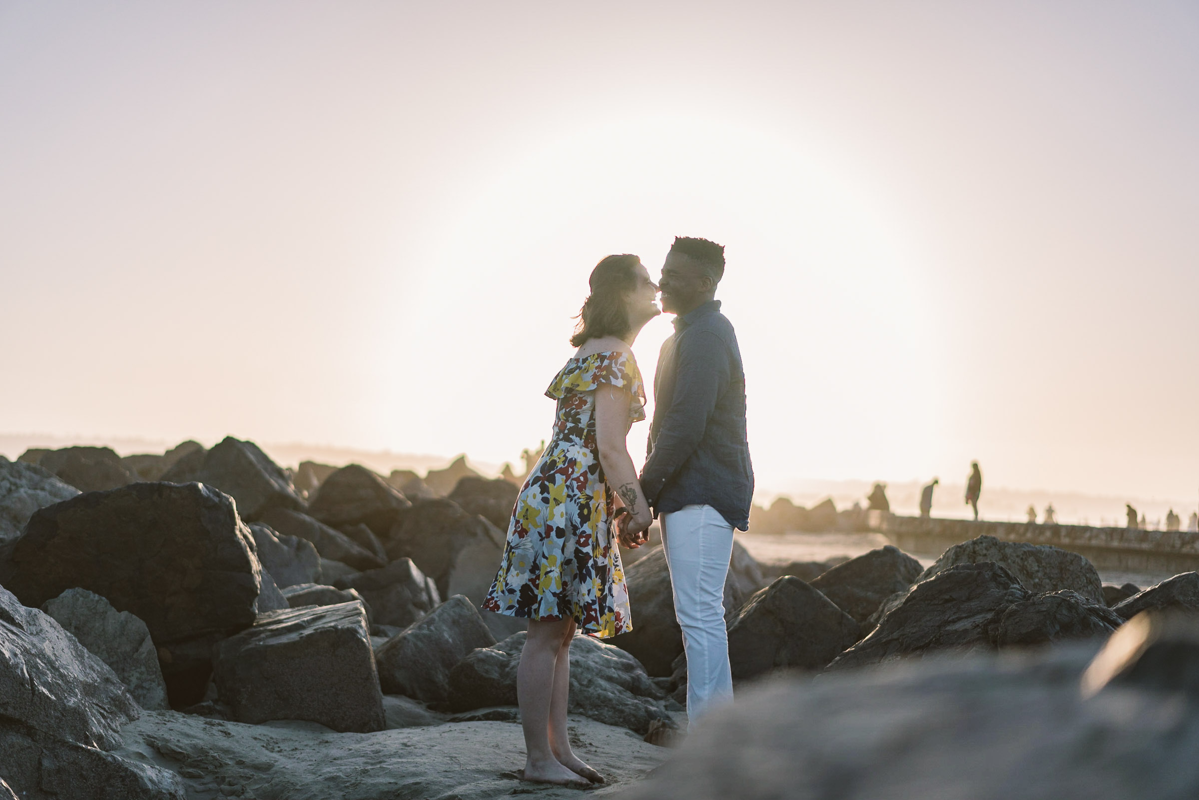 engagement session coronado island sunset san diego california white girl yellow blue red dress african american interracial couple rocks kiss laughing