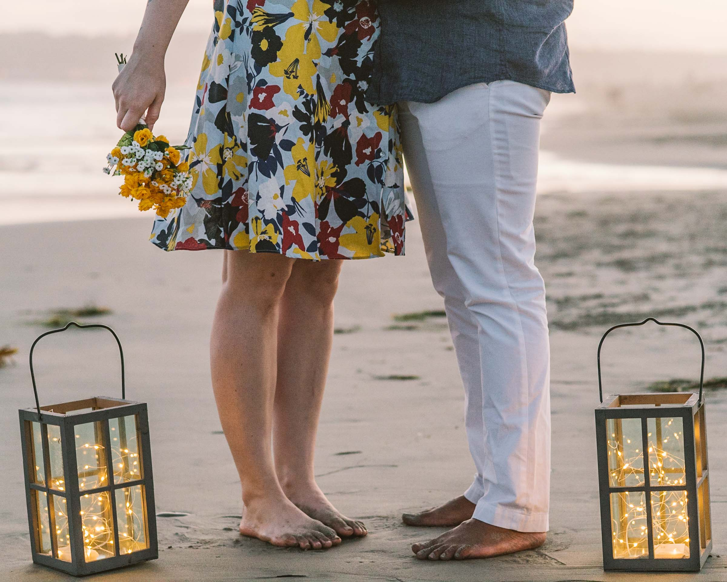 engagement session coronado island sunset san diego california white girl yellow flowers blue red dress african american interracial couple dusk feet lanterns pixie lights