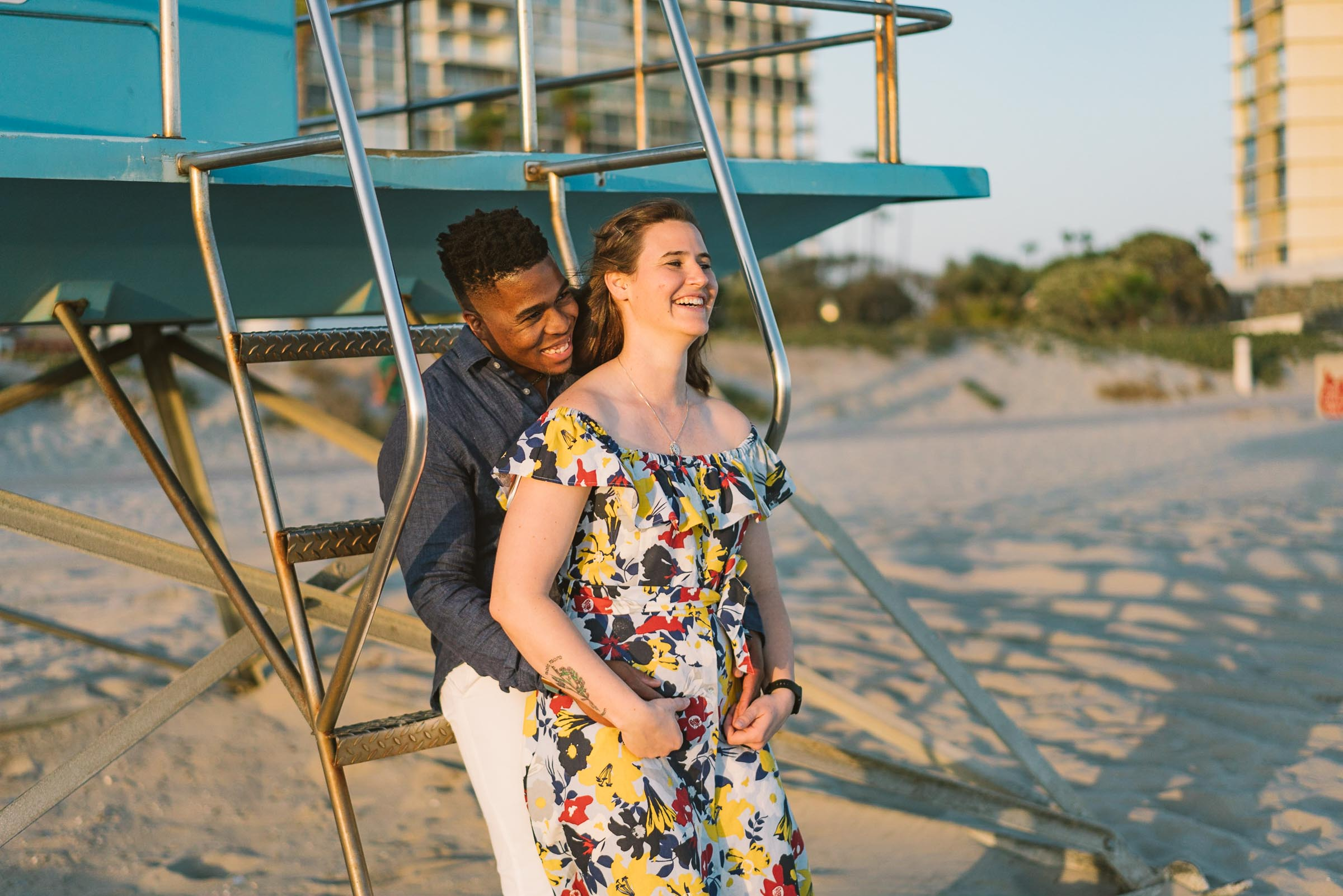 engagement session coronado lifeguard tower island sunset san diego california white girl yellow blue red dress african american interracial couple dusk