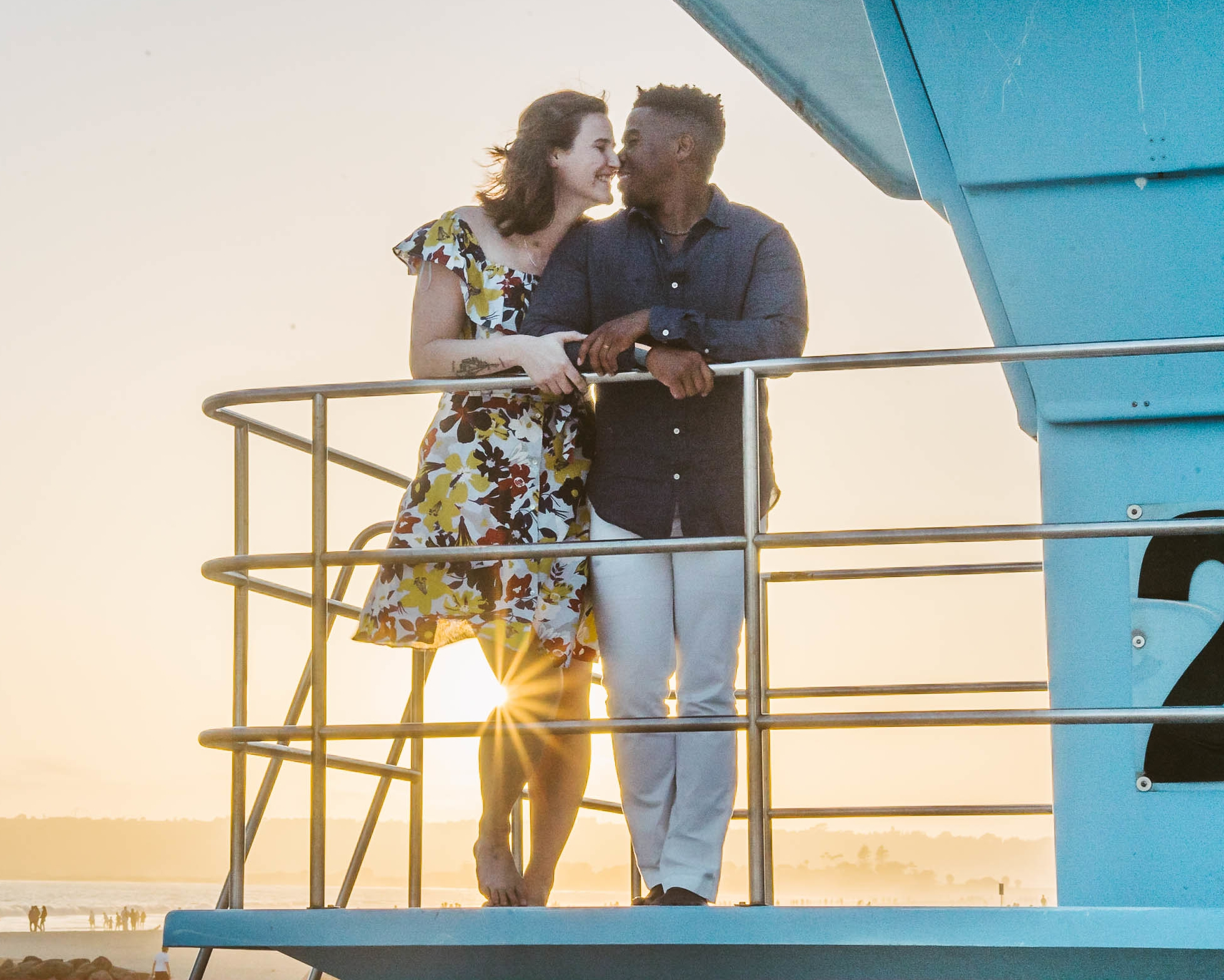 engagement session coronado lifeguard tower island sunset san diego california white girl yellow flowers blue red dress african american interracial couple dusk